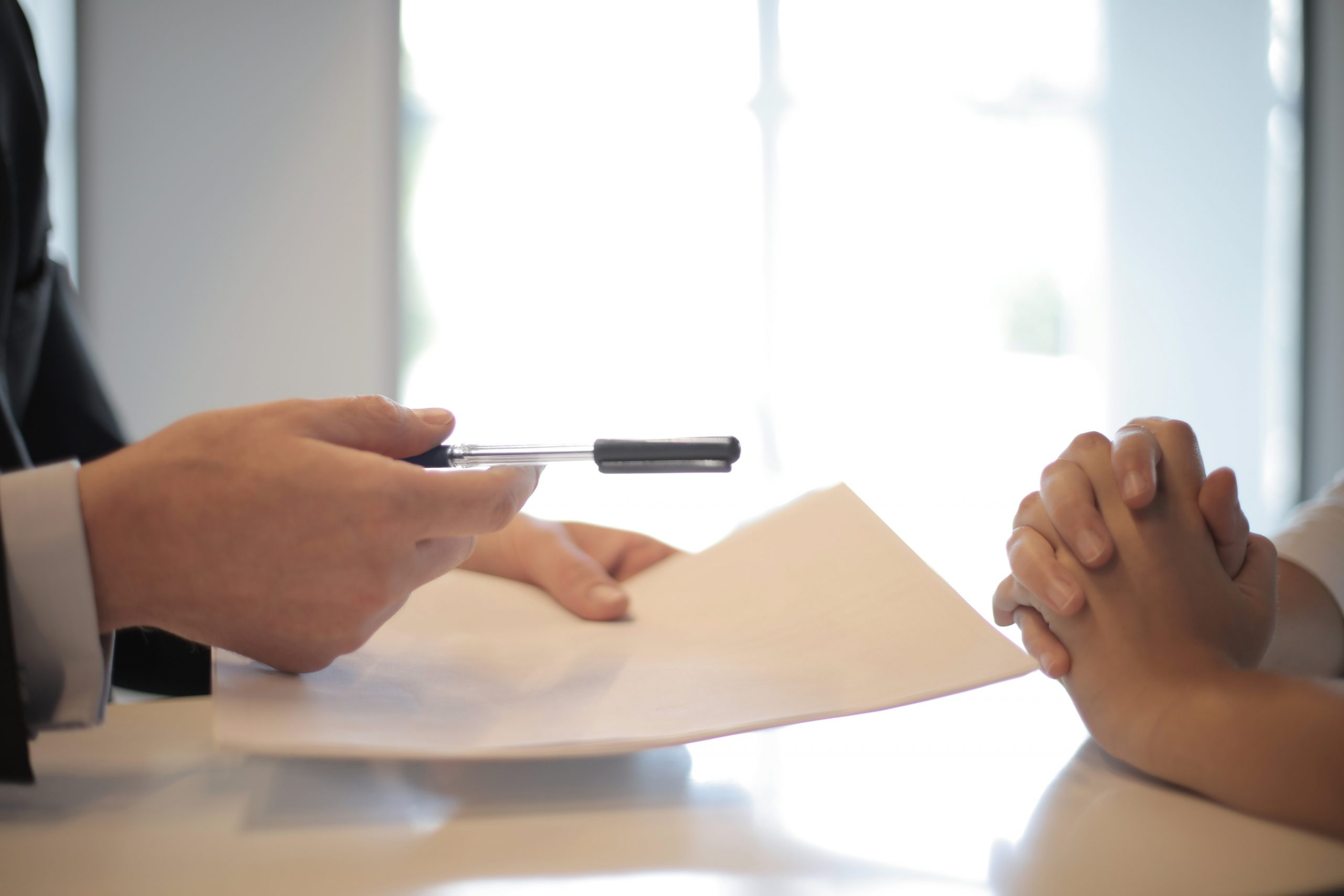 Man offering document and pen to other person